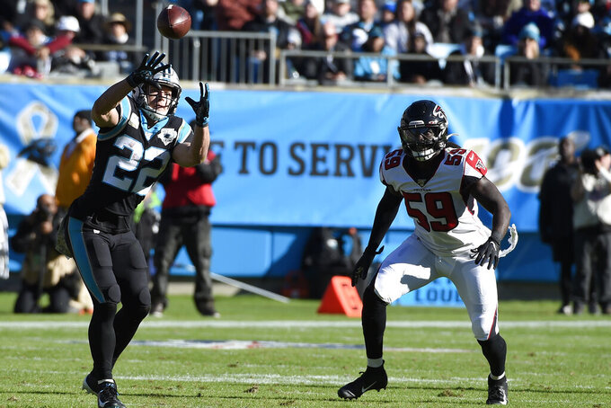 Carolina Panthers running back Christian McCaffrey (22) reaches for a pass while Atlanta Falcons outside linebacker De'Vondre Campbell (59) defends during the first half of an NFL football game in Charlotte, N.C., Sunday, Nov. 17, 2019. (AP Photo/Mike McCarn)
