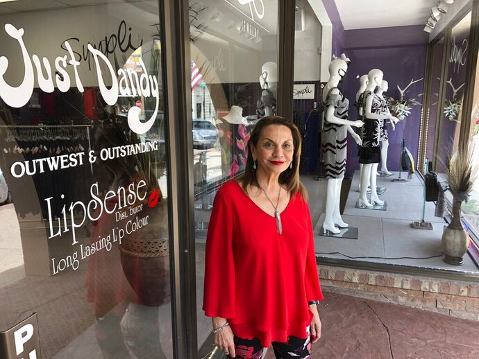 In this Thursday, May 28,2020 photo Virginia Binkerhoff stands outside the Just Dandy women's clothing store she owns in downtown Cheyenne, Wyo. The cancellation of this summer's Cheyenne Frontier Days rodeo and cowboy festival due to the coronavirus portends more hard times ahead for businesses struggling in Wyoming's capital city. (AP Photo/Mead Gruver)