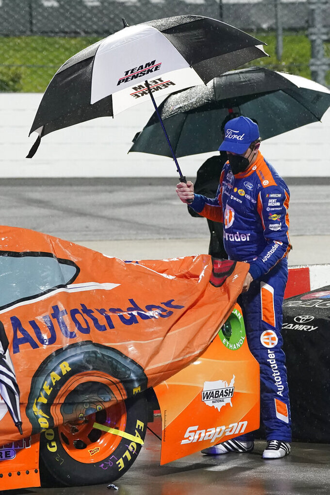 Brad Keselowski helps to cover his car during a rain delay at the NASCAR Cup Series auto race at Martinsville Speedway in Martinsville, Va., Saturday, April 10, 2021. (AP Photo/Steve Helber)
