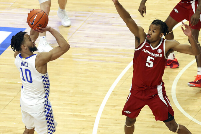 Kentucky's Davion Mintz hits a three point shot over Arkansas' Moses Moody (5) late in the second half of an NCAA college basketball game in Lexington, Ky., Tuesday, Feb. 9, 2021. (AP Photo/James Crisp)