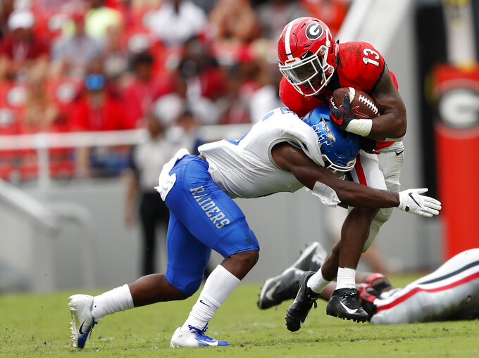 Georgia running back Elijah Holyfield (13) is stopped by Middle Tennessee linebacker Khalil Brooks (6) after a gain in the first half of an NCAA college football game Saturday, Sept. 15, 2018, in Athens, Ga. (AP Photo/John Bazemore)