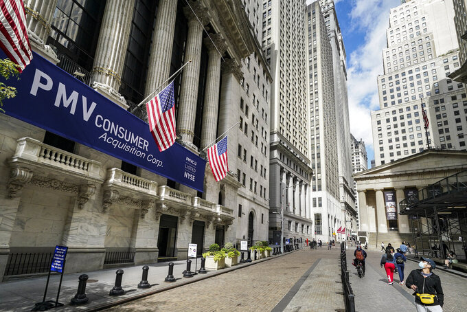 FILE - Pedestrians pass the New York Stock Exchange, Friday, Oct. 2, 2020, in New York.    Stocks are ticking higher on Wall Street Wednesday, Dec. 23,  following a mixed set of reports on the economy.   (AP Photo/John Minchillo)