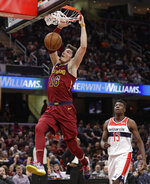 Cleveland Cavaliers' Cedi Osman dunks in front of Washington Wizards' Thomas Bryant during the first half of an NBA basketball game Saturday, Dec. 8, 2018, in Cleveland. (AP Photo/Tony Dejak)