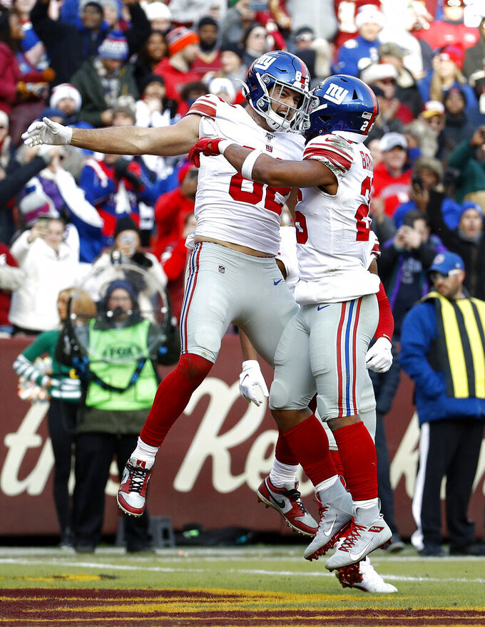 New York Giants tight end Kaden Smith, left, celebrates his touchdown catch with running back Saquon Barkley, right, during the second half of an NFL football game against the Washington Redskins, Sunday, Dec. 22, 2019, in Landover, Md. (AP Photo/Patrick Semansky)