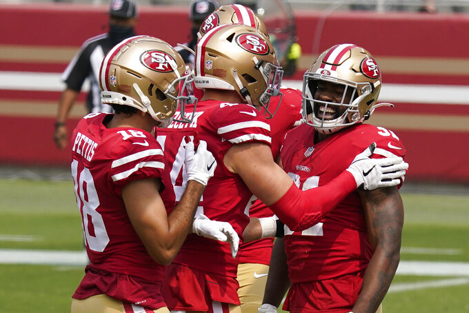 San Francisco 49ers running back Raheem Mostert, right, celebrates with teammates after scoring against the Arizona Cardinals during the first half of an NFL football game in Santa Clara, Calif., Sunday, Sept. 13, 2020. (AP Photo/Tony Avelar)