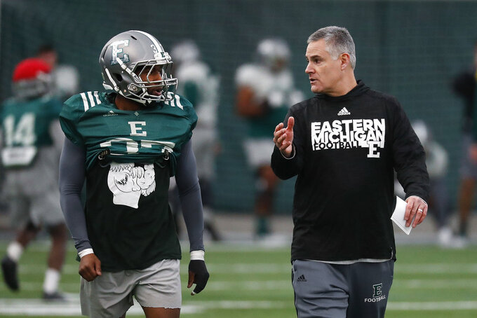 Eastern Michigan football coach Chris Creighton talks with Kymani Brown during practice in Ypsilanti, Mich., Monday, Dec. 10, 2018. Eastern Michigan's football team has stepped out of the shadows created by the neighboring University of Michigan and four professional teams just down the road in the Motor City. (AP Photo/Paul Sancya)