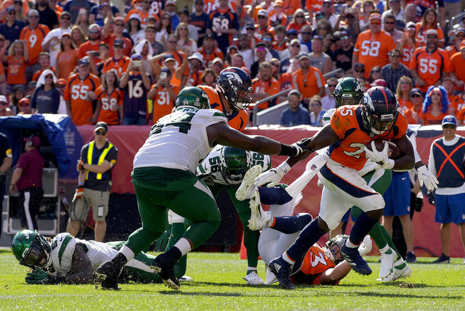 Denver Broncos running back Melvin Gordon (25) scores a touchdown as New York Jets defensive tackle Foley Fatukasi (94) defends during the first half of an NFL football game, Sunday, Sept. 26, 2021, in Denver. (AP Photo/David Zalubowski)