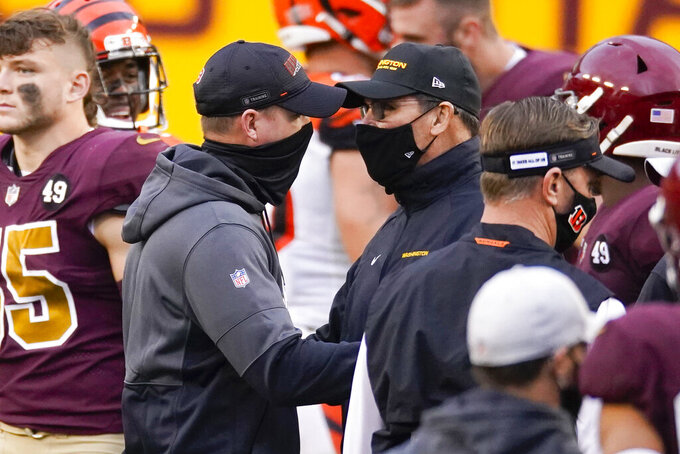 Cincinnati Bengals head coach Zac Taylor, left, and Washington Football Team head coach Ron Rivera, right, greet each other on the field at the end of an NFL football game between the Cincinnati Bengals and Washington Football Team, Sunday, Nov. 22, 2020, in Landover, Md. Washington won 20-9. (AP Photo/Al Drago)