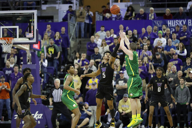 Oregon guard Payton Pritchard, right, shoots the game-winning 3-point basket as Washington guard Jamal Bey (5) tries for the block during overtime in an NCAA college basketball game, Saturday, Jan. 18, 2020, in Seattle. Oregon won 64-61 in overtime. (AP Photo/Ted S. Warren)