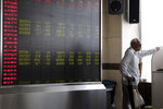 In this Wednesday, Sept. 25, 2019, photo, an elderly Chinese man stands near a display board for stock prices at a brokerage in Beijing. Asian stock markets followed Wall Street higher Thursday, Sept. 26, 2019, after U.S. President Donald Trump suggested a costly tariff war with China could be resolved soon. (AP Photo/Ng Han Guan)