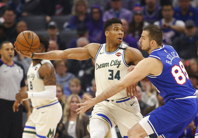 Milwaukee Bucks forward Giannis Antetokounmpo (34) keeps the ball out of the reach of Sacramento Kings forward Nemanja Bjelica, right, during the first quarter of an NBA basketball game in Sacramento, Calif., Friday, Jan. 10, 2020. (AP Photo/Rich Pedroncelli)