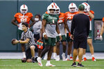 Miami quarterback D'Eriq King (1) walks on the field during NCAA college football practice Tuesday, Aug. 10, 2021, in Coral Gables, Fla. (AP Photo/Lynne Sladky)