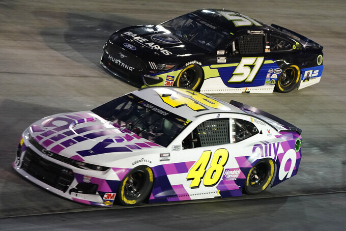Jimmie Johnson (48) and Joey Gase (51) drive into Turn 1 during the NASCAR Cup Series auto race Saturday, Sept. 19, 2020, in Bristol, Tenn. (AP Photo/Steve Helber)