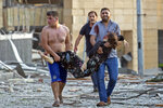 FILE - In this Aug. 4, 2020 file photo, Sedra Kinno, is carried by her brother Qoteiba, left, and her brother in law Fawaz in the aftermath of the massive explosion at the port  in Beirut, Lebanon. The Kinno family from Syria's Aleppo region was devastated in the wake of the explosion -- Sedra, 15, died in the explosion, while her sister Hoda, 11, survived with a broken neck and other injuries. (AP Photo/Hassan Ammar, File)
