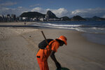 Gloria Maria cleans the shore of an unusually empty Copacabana beach backdropped by the Sugar Loaf Mountain in Rio de Janeiro, Brazil, Thursday, March 26, 2020, as people stay indoors to help contain the spread of the new coronavirus. The 41-year-old city worker said that in her 10 years of work cleaning the beach, she never saw an empty beach on a sunny Thursday.