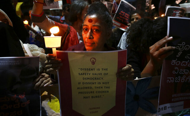 In this Tuesday, Feb. 4, 2020 photo, an Indian woman holds a candle and placard during a protest against the sedition case filed by police against a school after a play preformed by students denouncing a new citizenship law, in Bangalore, India. Critics, intellectuals, human rights activists, filmmakers, students and journalists in seen as opposed to Indian Prime Minister Narendra Modi's government are being increasingly silenced under a colonial-era sedition law. Official data reveal as many as 332 people were arrested under the law between 2016 and 2018, though only seven were convicted, suggesting that the police have struggled to gather evidence against the accused. (AP Photo/Aijaz Rahi)