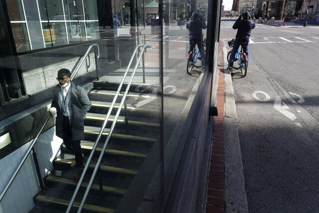 A passer-by, left, descends a stairway into a subway station, Tuesday, April 14, 2020, in Boston. The Boston area transit system is projecting a huge budget deficit for the fiscal year that ends June 30 caused in large part by a near non-existent ridership during the coronavirus crisis. (AP Photo/Steven Senne)