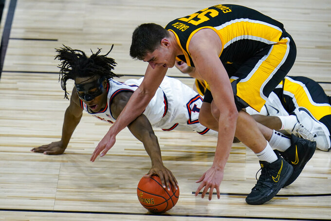 Illinois guard Ayo Dosunmu (11) dives for the ball under Iowa center Luka Garza (55) in the first half of an NCAA college basketball game at the Big Ten Conference tournament in Indianapolis, Saturday, March 13, 2021. (AP Photo/Michael Conroy)