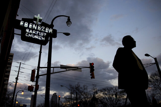 FILE - In this early Monday, Jan. 16, 2017 file photo, a man walks past the Ebenezer Baptist Church in Atlanta. The historic congregation at the heart of Atlanta, where the Rev. Martin Luther King Jr. had preached, sits at the intersection of national politics and the fate of a handful of pressing national policy fights. (AP Photo/Branden Camp)