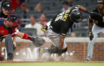 Pittsburgh Pirates' Gregory Polanco scores past the tag from Atlanta Braves catcher Tyler Flowers on a Corey Dickerson sacrifice fly during the sixth inning of a baseball game Wednesday, June 12, 2019, in Atlanta. (AP Photo/John Bazemore)