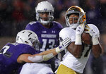 Notre Dame's Michael Young, right, makes a catch on his way to score a touchdown as he breaks away from Northwestern's Travis Jack Whillock, left, as Northwestern's JR Pace looks on during the second half of an NCAA college football game Saturday, Nov. 3, 2018, in Evanston, Ill. (AP Photo/Jim Young)