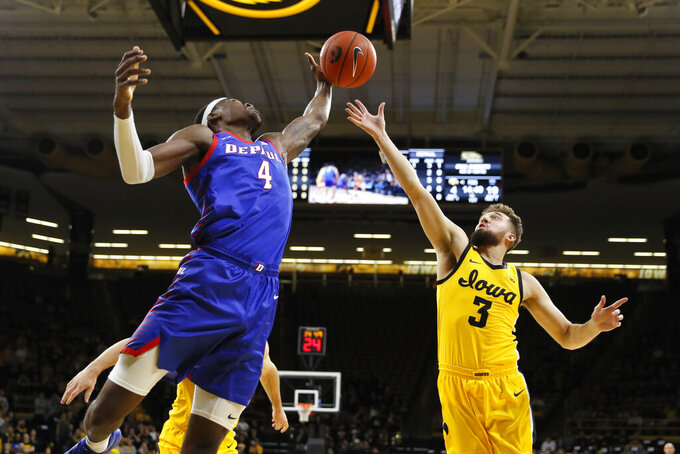 DePaul forward Paul Reed (4) fights for a rebound with Iowa guard Jordan Bohannon (3) during the first half of an NCAA college basketball game, Monday, Nov. 11, 2019, in Iowa City, Iowa. (AP Photo/Charlie Neibergall)