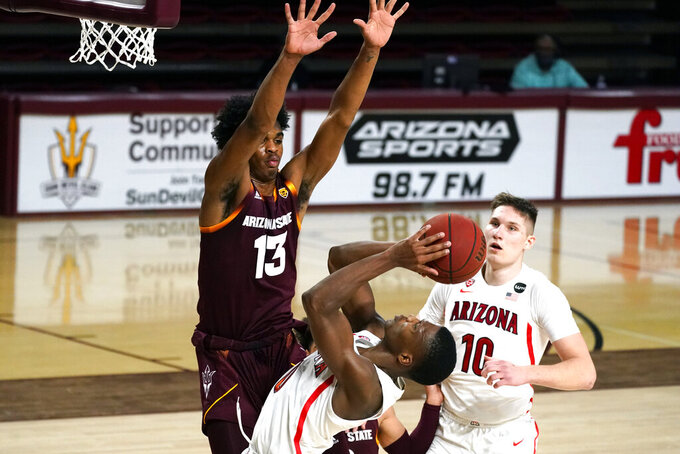 Arizona guard Bennedict Mathurin (0) scores against Arizona State guard Josh Christopher (13) during the second half of an NCAA college basketball game Thursday, Jan. 21, 2021, in Tempe, Ariz. Arizona won 84-82. (AP Photo/Rick Scuteri)