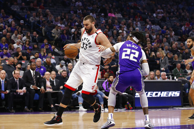 Toronto Raptors center Marc Gasol, left, tries to drive around Sacramento Kings center Richaun Holmes, right, during the first quarter of an NBA basketball game in Sacramento, Calif., Sunday, March 8, 2020. (AP Photo/Rich Pedroncelli)
