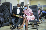 """Co-accused Callixte Nsabimana, right, popularly known as Sankara, speaks to his lawyer Moise Nkundabarashi, left, at the trial of Paul Rusesabagina, who boycotted the announcement of the verdict, at a court in Kigali, Rwanda Monday, Sept. 20, 2021. Rusesabagina, the man who inspired the film """"Hotel Rwanda"""" has been convicted of terrorism offenses and sentenced to 25 years in prison in a trial that human rights watchdogs and other critics of Rwanda's repressive government have described as an act of retaliation. (AP Photo/Muhizi Olivier)"""