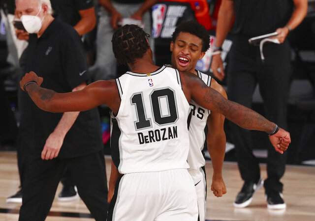 San Antonio Spurs forward DeMar DeRozan (10) celebrates with forward Keldon Johnson (3) after defeating the Sacramento Kings in an NBA basketball game Friday, July 31, 2020, in Lake Buena Vista, Fla. (Kim Klement/Pool Photo via AP)