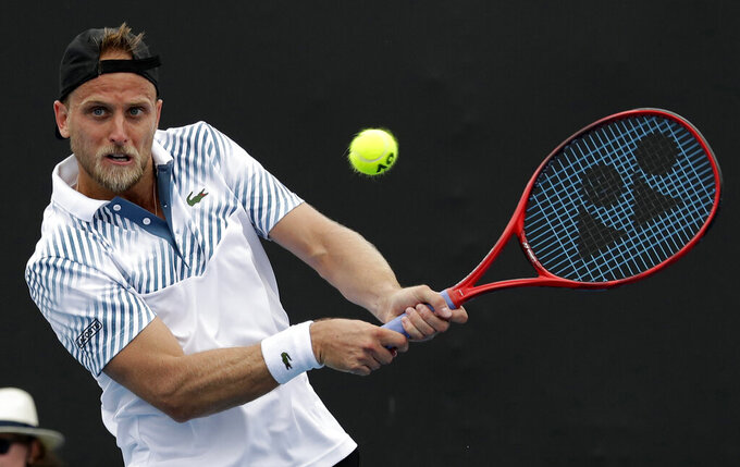 FILE - In this Jan. 16, 2019, file photo, the United States' Denis Kudla plays a backhand to Argentina's Diego Schwartzman during their second round match at the Australian Open tennis championships in Melbourne, Australia. Kudla has been withdrawn from Australian Open qualifying tournament in Doha, Qatar and put into hotel quarantine after returning positive tests for COVID-19, Monday, Jan. 11, 2021. (AP Photo/Aaron Favila, File)