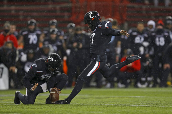 Cincinnati wide receiver Norman Love, left, holds as Cole Smith kicks the game winning field goal during the second half of the American Athletic Conference championship NCAA college football game against Tulsa, Saturday, Dec. 19, 2020, in Cincinnati. Cincinnati won 27-24. (AP Photo/Aaron Doster)