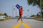 Temporary plant worker Shanuel Merevith, of Edmonson County, Ky., carries a sign and walks the picket line outside the as General Motors assembly plant in Bowling Green, Ky, Monday, Sept. 16, 2019. Thousands of members of the United Auto Workers walked off General Motors factory floors or set up picket lines early Monday as contract talks with the company deteriorated into a strike. (AP Photo/Bryan Woolston)