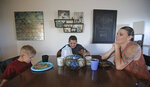 Misty Dotson shares dinner with her son's at their home Tuesday, Aug. 20, 2019, in Murray, Utah. Dotson is a 33-year-old single mother of two boys, ages 12 and 6, who goes to Planned Parenthood for care through the Title X program. Dotson is among the 39,000 people received treatment from Planned Parenthood of Utah in 2018 under a federal family planning program called Title X. The organization this week announced it is pulling out program rather than abide by a new Trump administration rule prohibiting clinics from referring women for abortions. (AP Photo/Rick Bowmer)