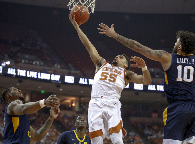 Texas guard Elijah Mitrou-Long (55) shoots the ball as West Virginia guard Jermaine Haley (10) defends during an NCAA college basketball game on Saturday, Jan. 5, 2019, in Austin, Texas. (Nick Wagner/Austin American-Statesman via AP)