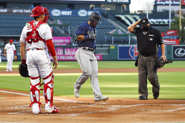 Seattle Mariners' Jose Marmolejos, center, touches home after hitting a three-run home run as Los Angeles Angels catcher Max Stassi, left, watches along with home plate umpire Doug Eddings during the first inning of a baseball game Thursday, July 30, 2020, in Anaheim, Calif. (AP Photo/Mark J. Terrill)