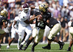 Colorado quarterback Brendon Lewis, front, rolls out to pass as Texas A&M defensive lineman DeMarvin Leal pursues in the first half of an NCAA college football game, Saturday, Sept. 11, 2021, in Denver. (AP Photo/David Zalubowski)
