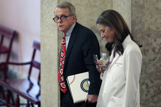 FILE - In this March 26, 2020, file photo Ohio Gov. Mike DeWine, left, and Dr. Amy Acton, director of the Ohio Department of Health, leave the State Room before their daily update on the states response to the ongoing COVID-19 pandemic at the Ohio Statehouse in Columbus, Ohio. DeWine is ready to mark one year of fighting the coronavirus pandemic. It was 12 months ago Wednesday, March 3, 2021, that he laid down strict attendance limits on the annual Arnold Sports Festival in Columbus, which brings thousands of people to the capital city.  (Joshua A. Bickel/The Columbus Dispatch via AP, File)