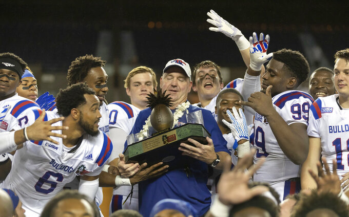 Louisiana Tech head coach Skip Holtz, surrounded by his team players, holds the Hawaii Bowl championship trophy after a Hawaii Bowl NCAA college football game against Hawaii, Saturday, Dec. 22, 2018, in Honolulu. Louisiana Tech beat Hawaii 31-14. (AP Photo/Eugene Tanner)