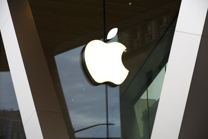 FILE - In this Saturday, March 14, 2020, file photo, an Apple logo adorns the facade of the downtown Brooklyn Apple store in New York. Demand for the iPhone drove Apple net income, which more than doubled in the January-March 2021 period as the tech giant continued to capitalize on smartphone addiction. (AP Photo/Kathy Willens, File)