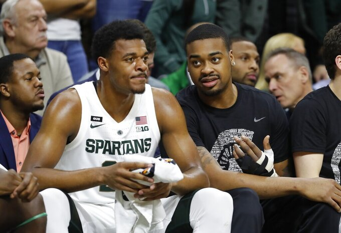 Michigan State forwards Nick Ward. right, and Xavier Tillman talk during the first half of the team's NCAA college basketball game against Rutgers, Wednesday, Feb. 20, 2019, in East Lansing, Mich. (AP Photo/Carlos Osorio)