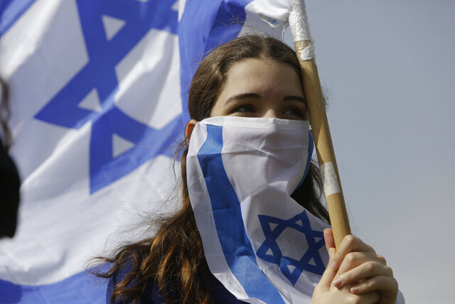 Israeli woman holds national flag during a protest against Prime Minister Benjamin Netanyahu outside the national parliament in Jerusalem, Monday, March 23, 2020. The opposition has accused Netanyahu of using the coronavirus crisis as cover to undermine the country's democratic institutions. With the country in near-shutdown mode, Netanyahu has already managed to postpone his own pending criminal trial and authorize unprecedented electronic surveillance of Israeli citizens. (AP Photo/Sebastian Scheiner)