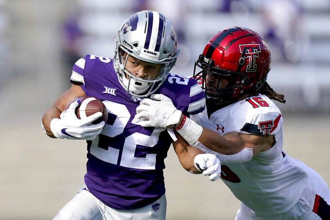 Kansas State running back Deuce Vaughn (22) is pulled down by Texas Tech defensive back Thomas Leggett (16) as he runs for a first down during the first half of an NCAA college football game Saturday, Oct. 3, 2020, in Manhattan, Kan. (AP Photo/Charlie Riedel)