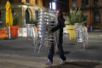 Chairs are cleared away outside a bar in Manchester's Northern Quarter, England, Thursday Oct. 22, 2020, as strict coronavirus restrictions on England's second-largest urban area, Greater Manchester, will start at midnight. (AP Photo/Jon Super)