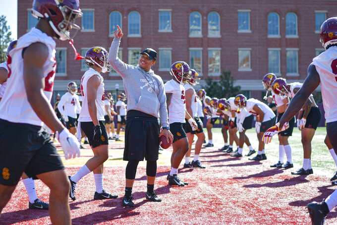 In this undated photo provided by the University of Southern California Athletics,  USC associate coach Donte Williams , center, reacts during NCAA college football practice in Los Angeles. Williams, the Trojans' cornerbacks coach and associate head coach, is taking over for the rest of the season alongside offensive coordinator Graham Harrell and defensive coordinator Todd Orlando, after the school fired head coach Clay Helton on Monday, Sept. 13, 2021. (John McGillen/University of Southern California Athletics via AP)