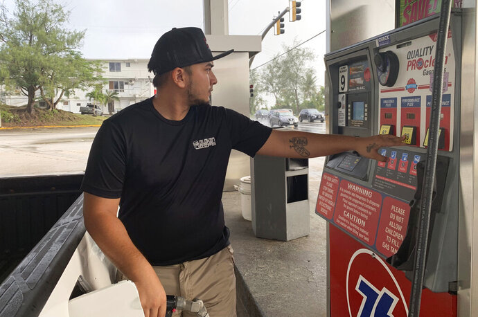 Jared Duenas fills up his pickup truck with gasoline in the village of Sinajana, Guam in preparation of a typhoon on Thursday, Feb. 21, 2019.  An intensifying tropical storm in the Pacific is bearing down on Micronesia and could threaten the U.S. territory of Guam in the coming days.  (AP Photo/Grace Garces Bordallo)