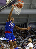 Kansas guard Ochai Agbaji (30) dunks the ball over TCU's Alex Robinson, bottom right, in the first half of an NCAA college basketball game in Fort Worth, Texas, Monday, Feb. 11, 2019. (AP Photo/Tony Gutierrez)