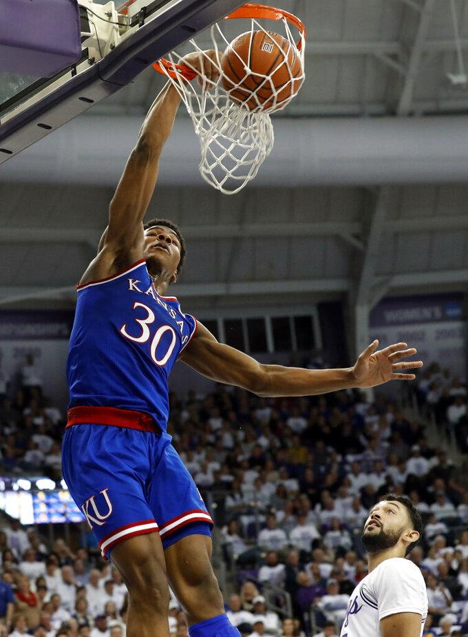 Kansas guard Ochai Agbaji (30) dunks the ball over TCU's Alex Robinson, bottom right, in the first half of an NCAA college basketball game in Fort Worth, Texas, Monday, Feb. 11, 2019. (AP Photo/Tony Gutierrez)