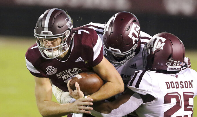 Mississippi State quarterback Nick Fitzgerald (7) is tackled by Texas A&M defensive lineman Jayden Peevy, center and Tyrel Dodson (25) during the first half of their NCAA college football game on Saturday, Oct. 27, 2018, in Starkville, Miss. (AP Photo/Jim Lytle)