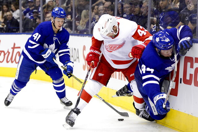 Toronto Maple Leafs left wing Dmytro Timashov (41) looks to take the puck as Detroit Red Wings left wing Darren Helm (43) sends Maple Leafs defenseman Morgan Rielly (44) into the boards during third-period NHL hockey game action in Toronto, Saturday, Dec. 21, 2019. (Frank Gunn/The Canadian Press via AP)